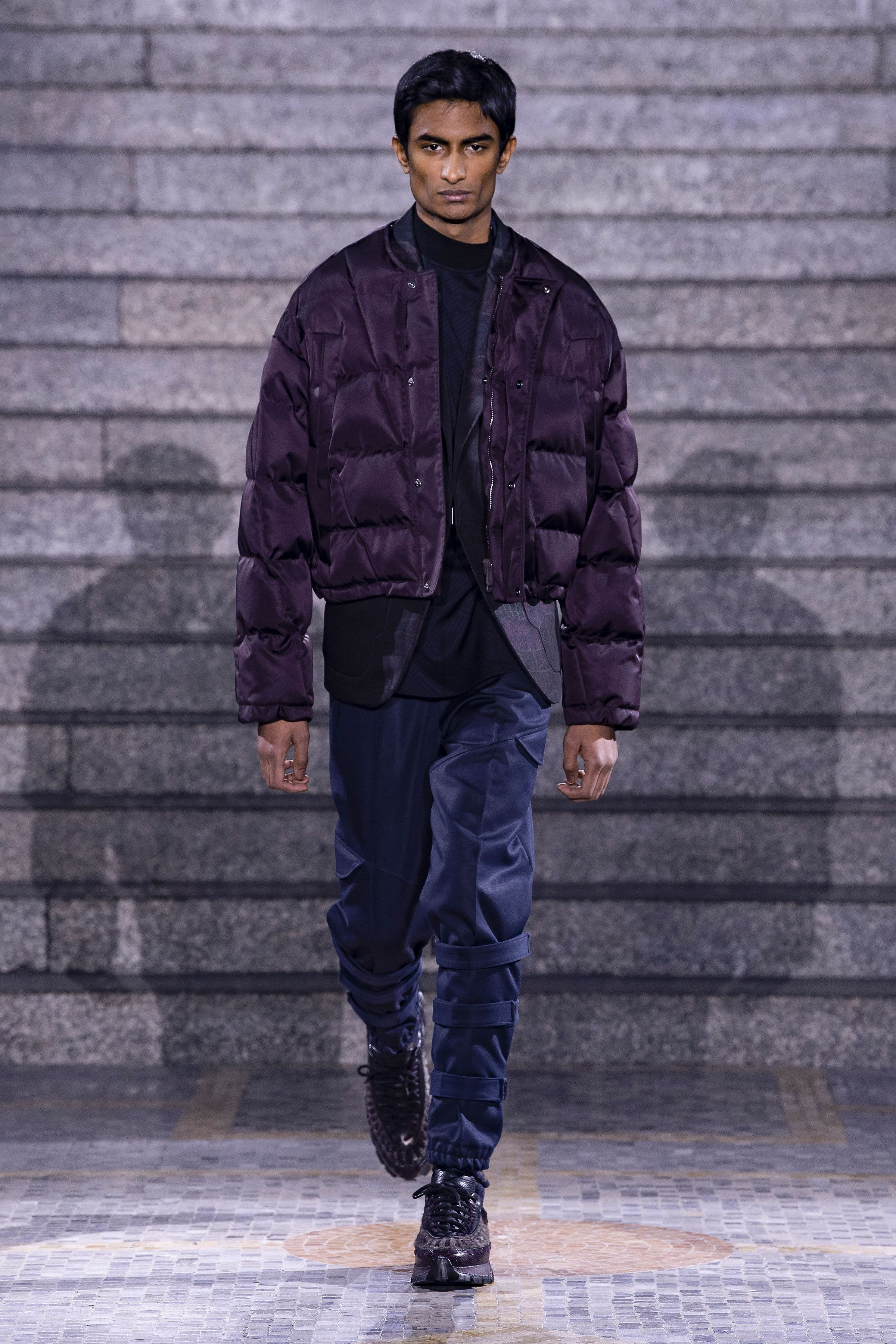 Over-sized purple gilet jacket worn over navy trousers and punk-rock themed boots.