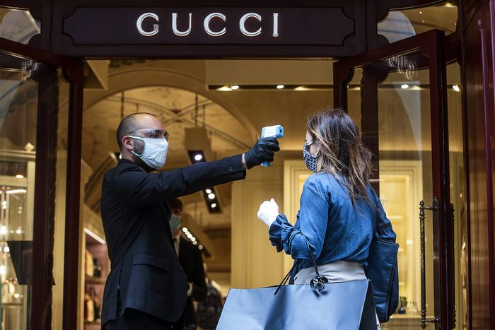 A temperature check being conducted outside a Gucci store in Italy. (Photo credit: Shutterstock)